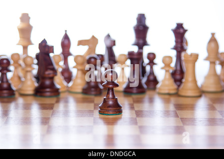 Beautiful chessboard with chessfigures in the back and a focused pawn in the front - Stock Photo
