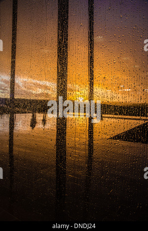 New visitors centre at Stonehenge in Wiltshire UK looking at the winter solstice sunset through rain covered glass - Stock Photo