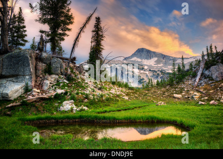Small pond reflecting Eagle Cap Mountain and sunset clouds. Eagle Cap wilderness, Oregon - Stock Photo