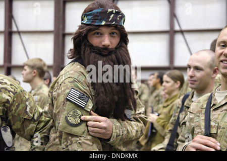 A US Army soldier wearing a fake beard waits for Duck Dynasty reality television star Willie Robertson December - Stock Photo