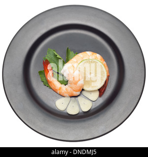 Shrimp with garlic and lime on black plate isolated on white backgorund - Stock Photo