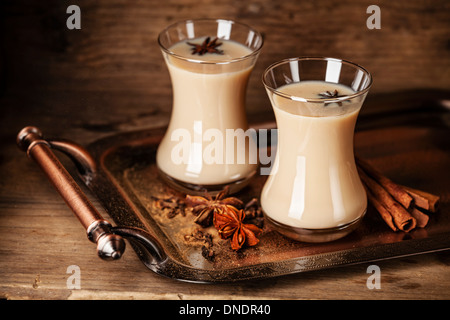 Hot tea with milk and spices on dark background - Stock Photo