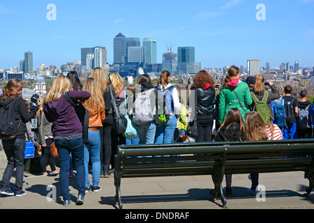 Group of girls & boys on educational visit to Greenwich park & Observatory looking at view towards Canary Wharf - Stock Photo