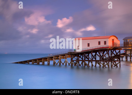 The old lifeboat station at Tenby, Pembrokeshire at dusk. A long exposure softens the waves in the sea. - Stock Photo