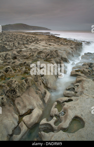 A trench in the rock formations at Dunraven Bay, South Wales, Channels the waves of the incoming tide. A long exposure - Stock Photo