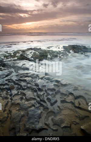 Rock formations at Dunraven Bay, South Wales, are caused by the power of the sea. The sun sets while the tide comes - Stock Photo