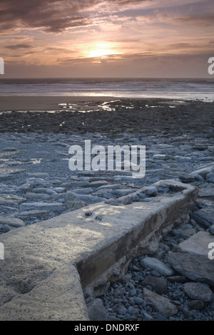 Rock formations at Dunraven Bay, South Wales, are caused by the power of the sea at sunset. - Stock Photo
