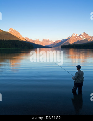Middle age male fly fishing on Maligne Lake, Jasper National Park, Alberta, Canada. - Stock Photo