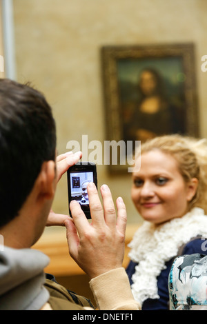 man taking photo of woman in front of the Mona Lisa painting by Leonardo da Vinci, Louvre Museum, Paris, France - Stock Photo