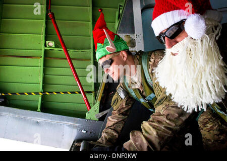 US Army special operation soldiers dressed in Christmas costumes watch the Afghanistan countryside from the tail - Stock Photo