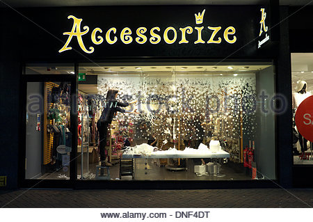 A shop worker removes Christmas decorations in the display window of retailer Accessorize, a fashion accessory retail - Stock Photo