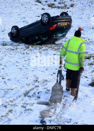 Buxton, Derbyshire, UK. 25th Dec, 2013. A car is recovered from a snowy hillside after sliding more than 150ft on - Stock Photo