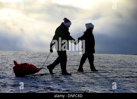 Buxton, Derbyshire, UK. 25th Dec, 2013.  After waking up to a white Christmas, Colin Chandler and Judith Irwin use - Stock Photo
