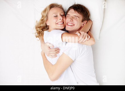 Two happy young dates lying in bed and embracing - Stock Photo