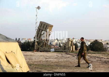 Jerusalem. 26th Dec, 2013. An Israeli soldier walks past an Iron Dome anti-missile battery near the Israeli southern - Stock Photo