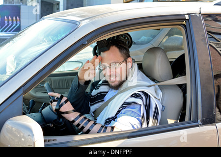 Portrait of a religious Jewish man in his car wearing phylacteries, skull cap & prayer shawl. In Crown Heights, - Stock Photo
