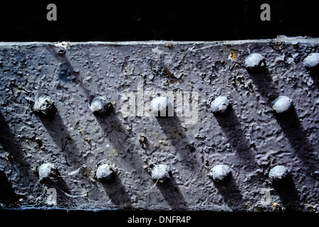 Metal rivets and girders on underside of bridge - Stock Photo
