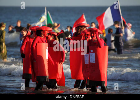 Women dressed as post boxes stand in the North Sea during the Boxing Day Dip at Sunderland, UK. Up to 1000 participants - Stock Photo
