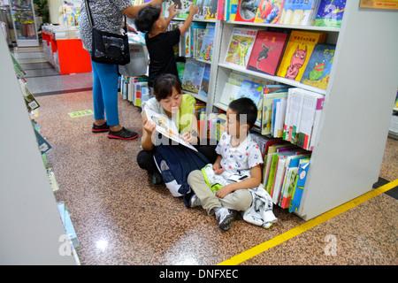 Beijing China Wangfujing Xinhua Bookstore shopping inside sale books shelves Asian woman mother boy son family reading - Stock Photo