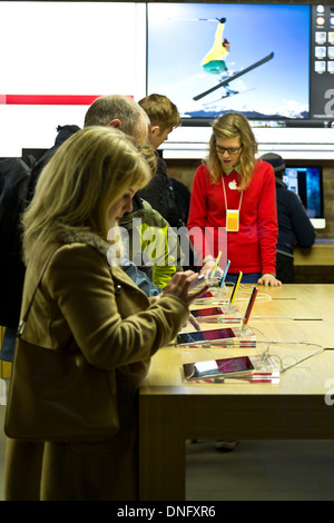 People trying out iPhones and iPads at the Apple Store Covent Garden, London, England - Stock Photo