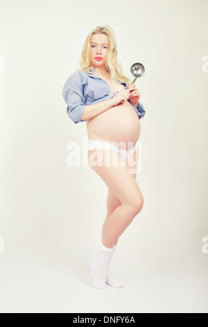 pretty pregnant woman posing with serving spoon - Stock Photo