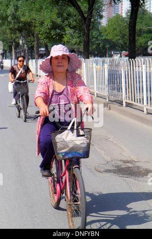 Beijing China Guang An Men Nei Da Jie Guanganmen Outer Street Asian woman riding bicycle - Stock Photo