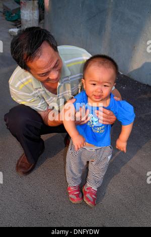 Beijing China Xicheng District Guang An Men Nei Da Jie Guanganmen Inner Street man boy grandfather grandson holding - Stock Photo