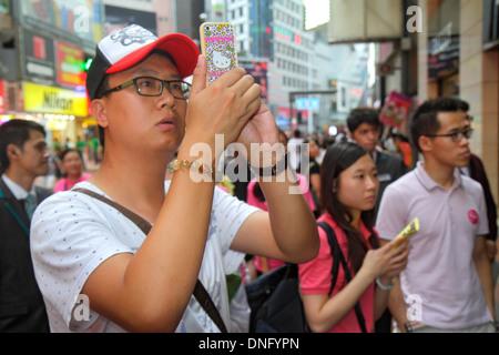 Hong Kong China Island Causeway Bay Yee Wo Street East Point Road Asian man smartphone camera taking picture - Stock Photo