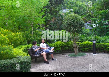 Hong Kong China Island Central Hong Kong Park landscape trees bench Asian man woman couple sitting - Stock Photo