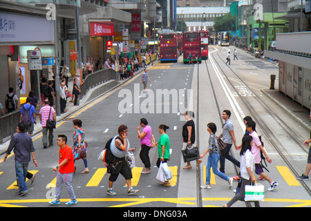 Hong Kong China Island Central Des Voeux Road Central pedestrians crossing street tracks Asian man woman - Stock Photo