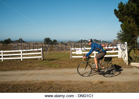 Backroads Cyclist Riding on Dirt Road at Chanslor Ranch, Bodega Bay, California - Stock Photo