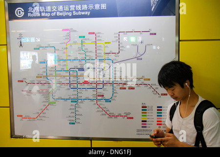 Beijing China Xuanwumen Subway Station public transportation passenger rider Asian man Line 4 platform waiting smartphone - Stock Photo