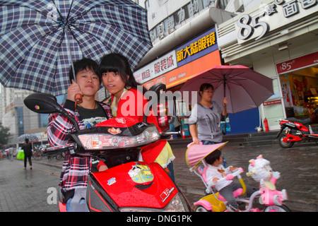 Beijing China Xicheng District Guang An Men Nei Da Jie Guanganmen Inner Street Asian man woman couple umbrella weather - Stock Photo
