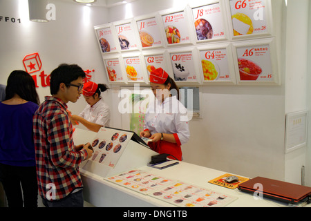 Beijing China The Malls at Oriental Plaza desserts fruit cups vendor counter Asian woman employee job uniform man - Stock Photo