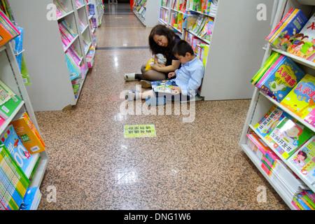 Beijing China Wangfujing Xinhua Bookstore shopping inside sale books shelves Asian woman mother boy son family browsing - Stock Photo