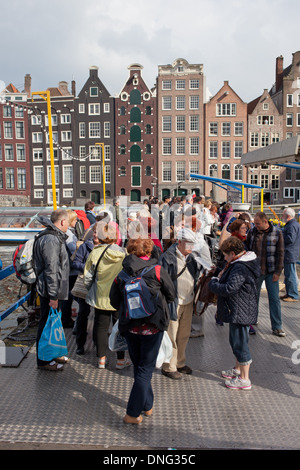 Group of tourists waiting at a canal boat tours pier in the Old Town of Amsterdam, Holland, the Netherlands. - Stock Photo