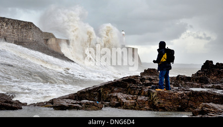 An onlooker witnesses huge waves crash over Porhcawl harbor wall and lighthouse, South Wales. - Stock Photo