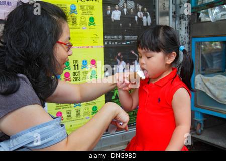 Hong Kong China Kowloon Prince Edward Nathan Road Asian woman mother girl daughter licking eating ice cream cone - Stock Photo
