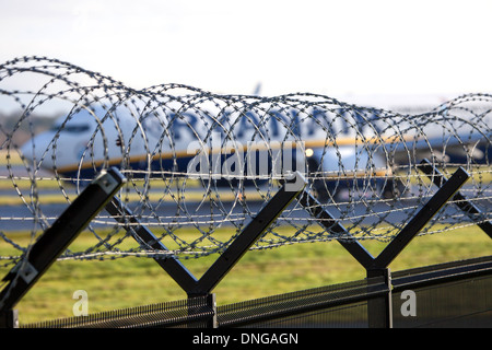 Security fence with barber razer wire in front of an ryanair aeroplane - Stock Photo