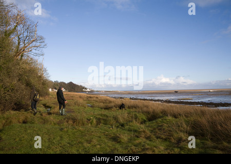 Red Wharf Bay Isle of Anglesey North Wales UK Two men walking a dog along the coastline towards the bay - Stock Photo