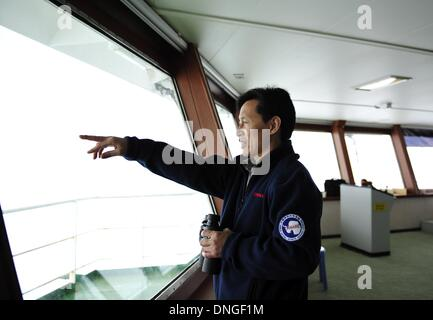 Aboard Xuelong, Snow Dragon. 28th Dec, 2013. Wang Jianzhong, captain of Xuelong, observes the weather condition - Stock Photo