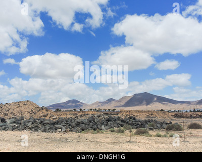 Fluffy Clouds over Volcanos in Lanzarote. A wire fence and signs of construction against the back drop of Spanish - Stock Photo