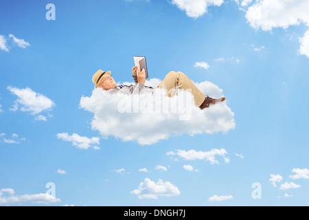 Senior male reading a book on clouds - Stock Photo