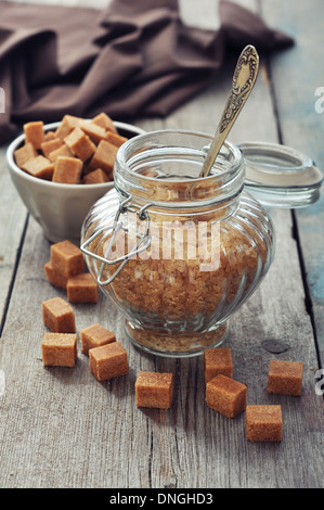 Brown candy sugar in glass jar on wooden background - Stock Photo