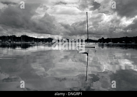 Reflection of sails boats yachts in marina waters under cloudy sky. (BW) - Stock Photo