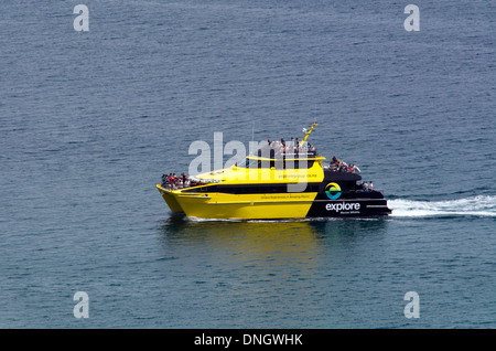 Visitors ride on a tourist explore boat in the Bay of Islands, New Zealand - Stock Photo