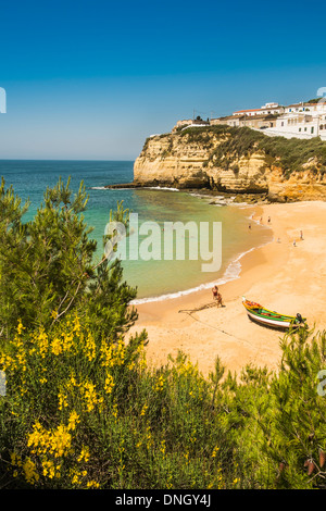 coloufully painted fishing boat and partial view of the village, carvoeiro, algarve, portugal - Stock Photo