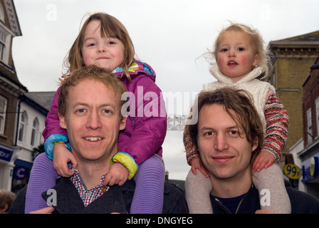 Fathers carrying their children on their shoulders at an annual christmas fayre, Petersfield, Hampshire, UK. - Stock Photo