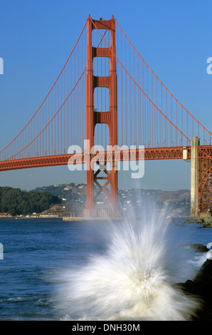 Golden Gate Bridge with waves crashing on rocks with warm light from Baker Beach, San Francisco, California USA - Stock Photo