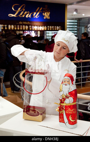 A Lindt Chocolate employee wrapping a chocolate Santa Claus, the Chocolate Museum, Cologne, Germany, Europe - Stock Photo